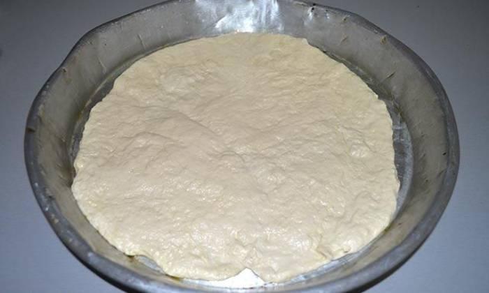 раскатанное тесто в форме для пиццы